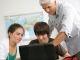 Portrait d'un jeune garçon et d'une fille devant un ordinateur portable en salle de cours près d'un homme //©Phovoir