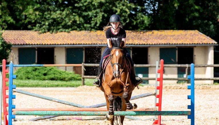 """Lucy participe aux compétitions en """"complet"""" (saut, cross et dressage). Ici, elle s'entraîne au saut d'obstacles."""