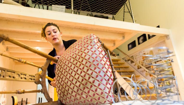 """<strong>LAURA, TAPISSIÈRE D'AMEUBLEMENT, REDONNE VIE AUX FAUTEUILS, CHAISES, BANQUETTES… (1/2)</strong><br />Telle est la vocation de Laura, 31 ans, tapissière d'ameublement. Formée en apprentissage, elle a repris ses études après une dizaine d'années d'expérience, pour décrocher le BTS design de produits. Elle """"opère"""" aussi bien des meubles très anciens que ceux des années 1980. Le travail traditionnel, en crin animal ou végétal (qui compose la plupart des assises anciennes), nécessite deux à trois fois plus de temps que le travail moderne, en mousse. """"Avant de montrer le résultat à un client, j'ai toujours peur… Mais c'est très plaisant quand on voit les yeux pétiller, les sourires jusqu'aux oreilles !"""" //&nbsp;&copy;&nbsp;Thomas Louapre / Divergence pour l&#039;Étudiant"""