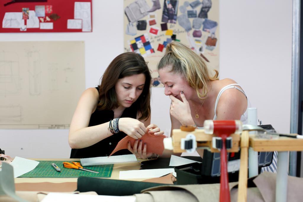 Césarie et Claire, élèves du BTS maroquinerie, échangent sur le tissu le plus approprié pour confectionner leur sac. //©Mathieu Cugnot/Divergence pour l'Etudiant