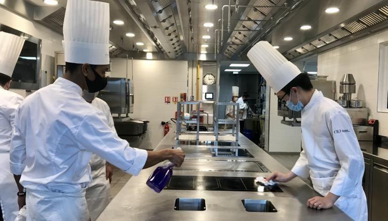 En cuisine, les normes sanitaires sont très strictes. Les étudiants désinfectent les surfaces plusieurs fois par jour.