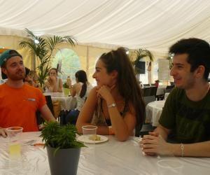 """Sous le chapiteau, l'équipe """"animation"""" représentée ici par Samuel, en orange, accueille et renseigne les candidats au concours Passerelle (Léa et Alexandre) autour d'une citronnade."""