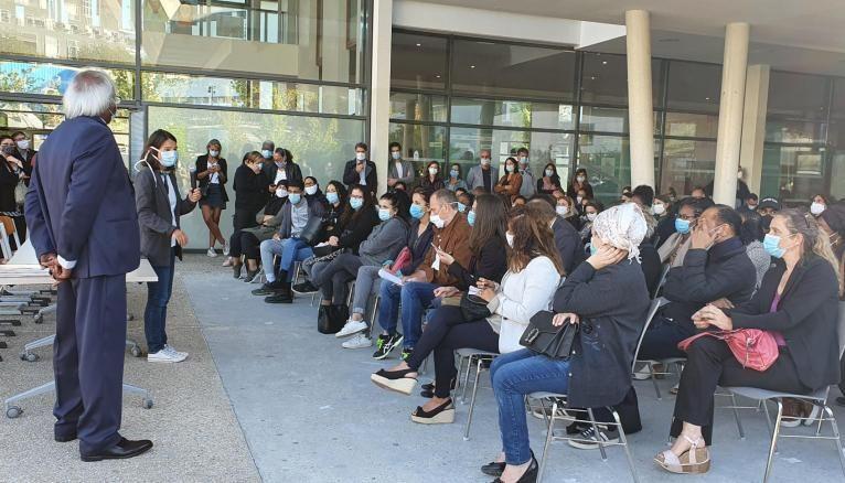 Rassemblés dans la cour du collège, les parents écoutent le discours du principal du collège Jean Renoir (de dos).