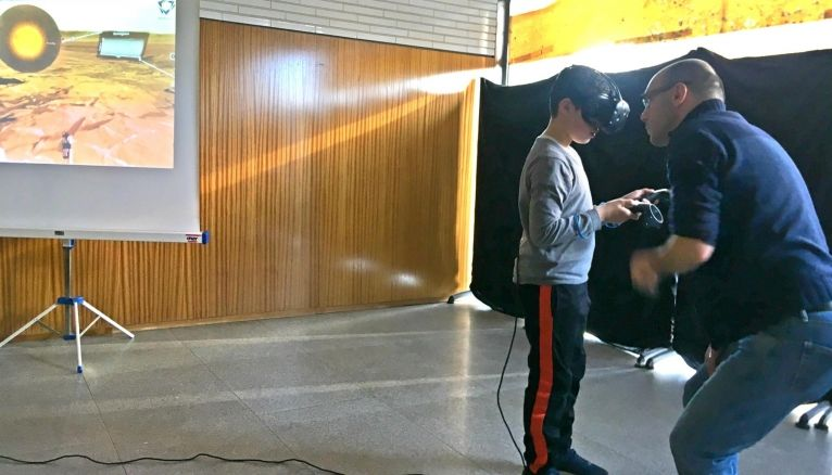Le jeune Mohamed, aidé de l'ingénieur de recherche, découvre une partie de Mars grâce à la réalité virtuelle.
